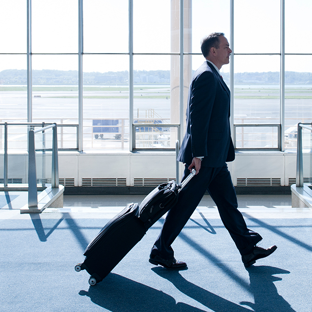 Business man with rolling suitcase walking in airport terminal.