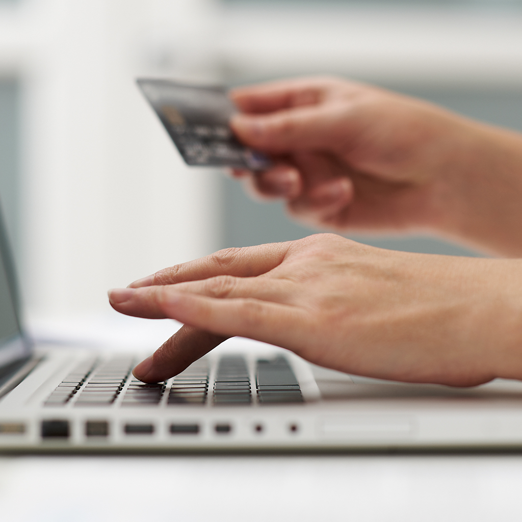 Close up of a woman on her laptop holding her Visa card